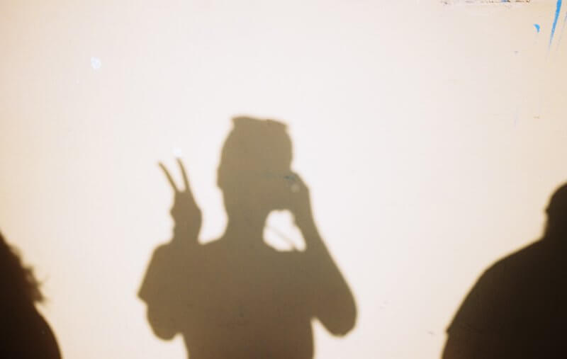 Silhouette of a person making a peace hand sign